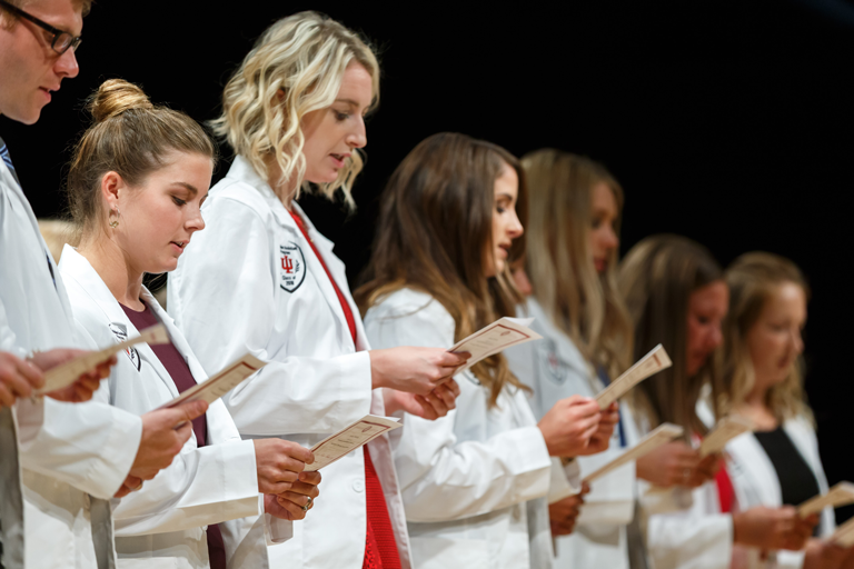 PA students pictured in white coats. They have 100 percent pass rate on national exams.