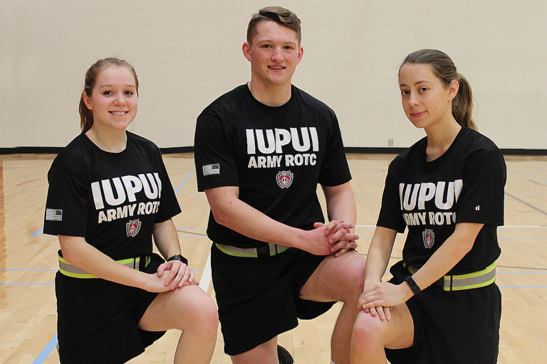 Three IUPUI ROTC students pose for a picture in the IUPUI gymnasium.