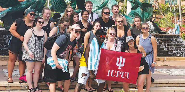 Tourism, event, and sport management students pose for a photo while visiting the Caribbean with IUPUI flag.