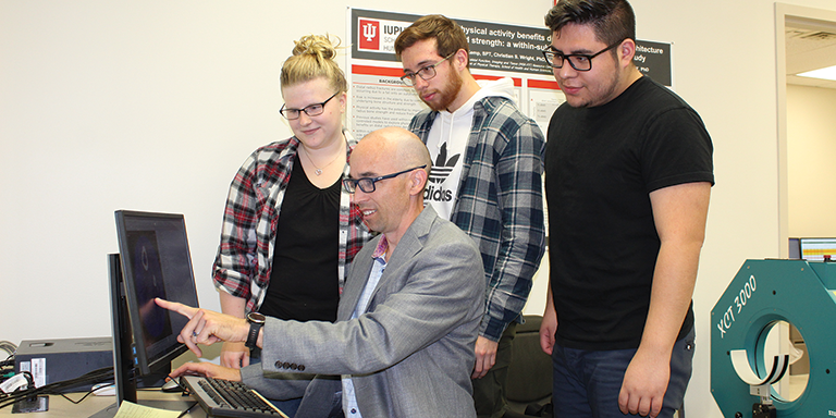 Associate Dean for Research Stuart Warden points to a computer screen and talks with students.