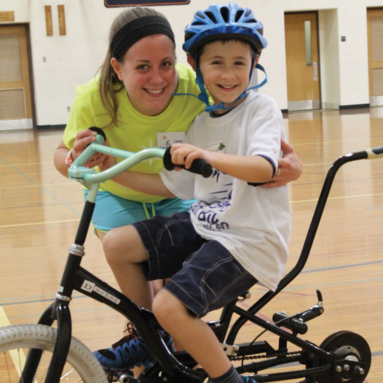 Larken seen here helping kids with disabilities ride bikes
