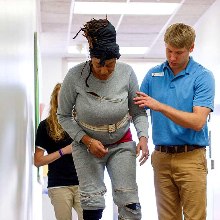 A student helps a person walk down a hallway.