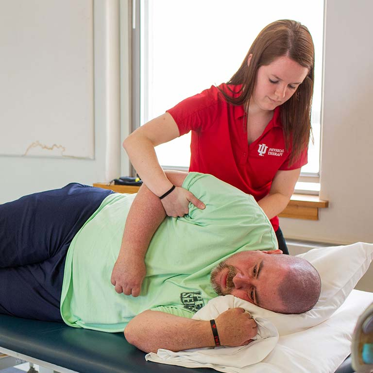 A student helps a patient who is laying on his side.