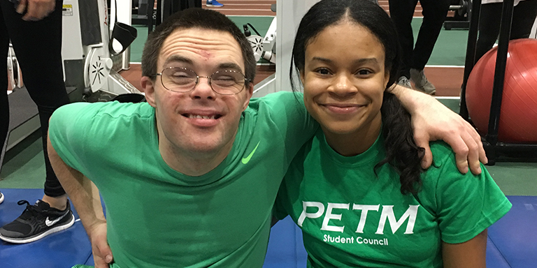 Volunteer and participant smile during an adapted movement clinic.