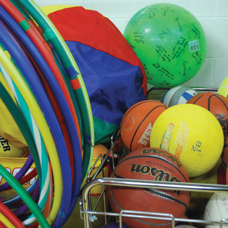 Red, yellow, blue, and green hula hoops and balls lay in a wire basket in a gymnasium.