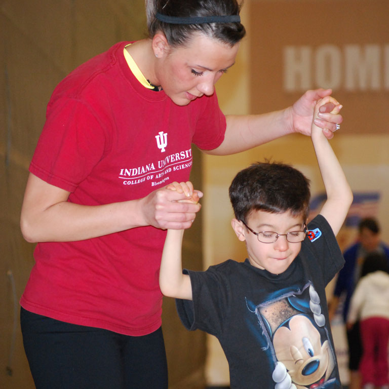 A female student helps a young child walk in the Motor Activity Clinic.