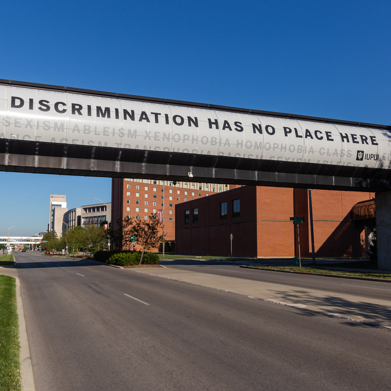 "A campus skywalk banner that says, ""discrimination has no place here"""