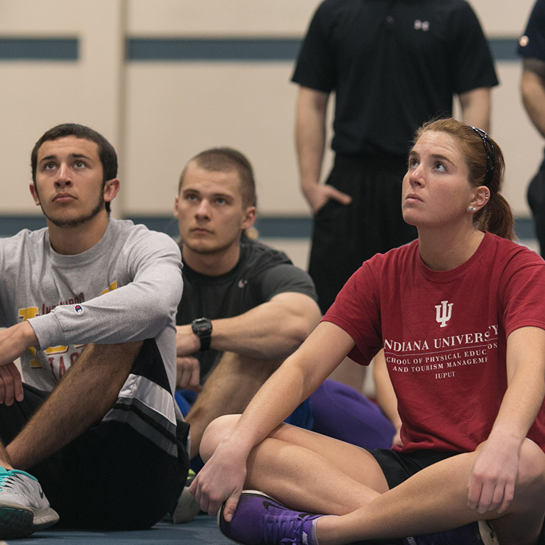 Kinesiology students listen to professional strength and conditioning instructors.